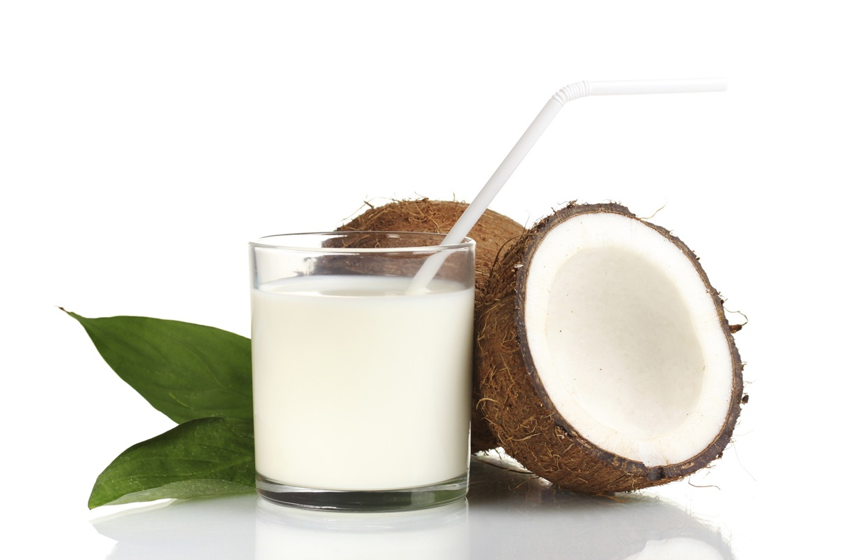 Glass of coconut milk next to open coconut