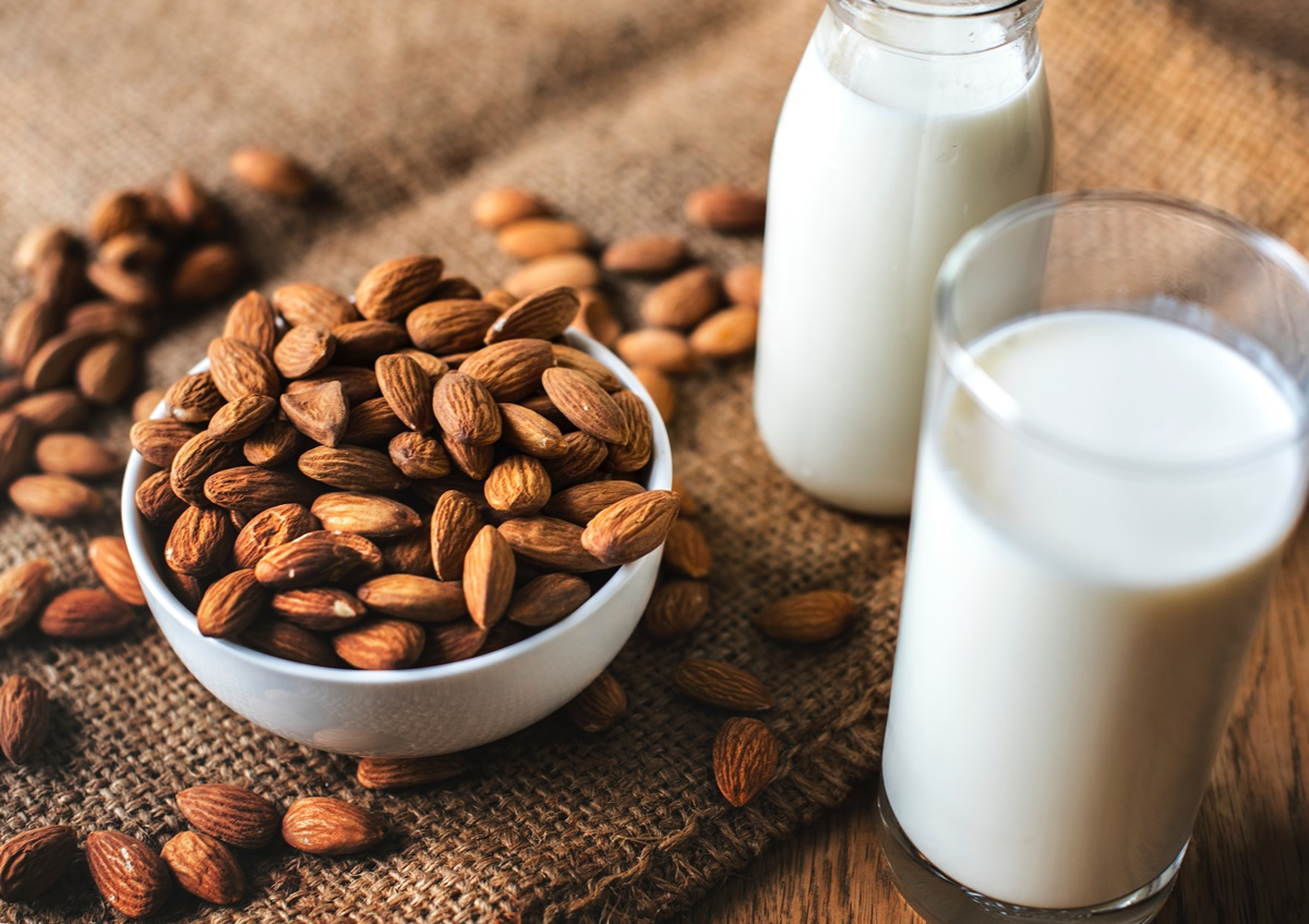 Almonds in a bowl next to glass of almond milk