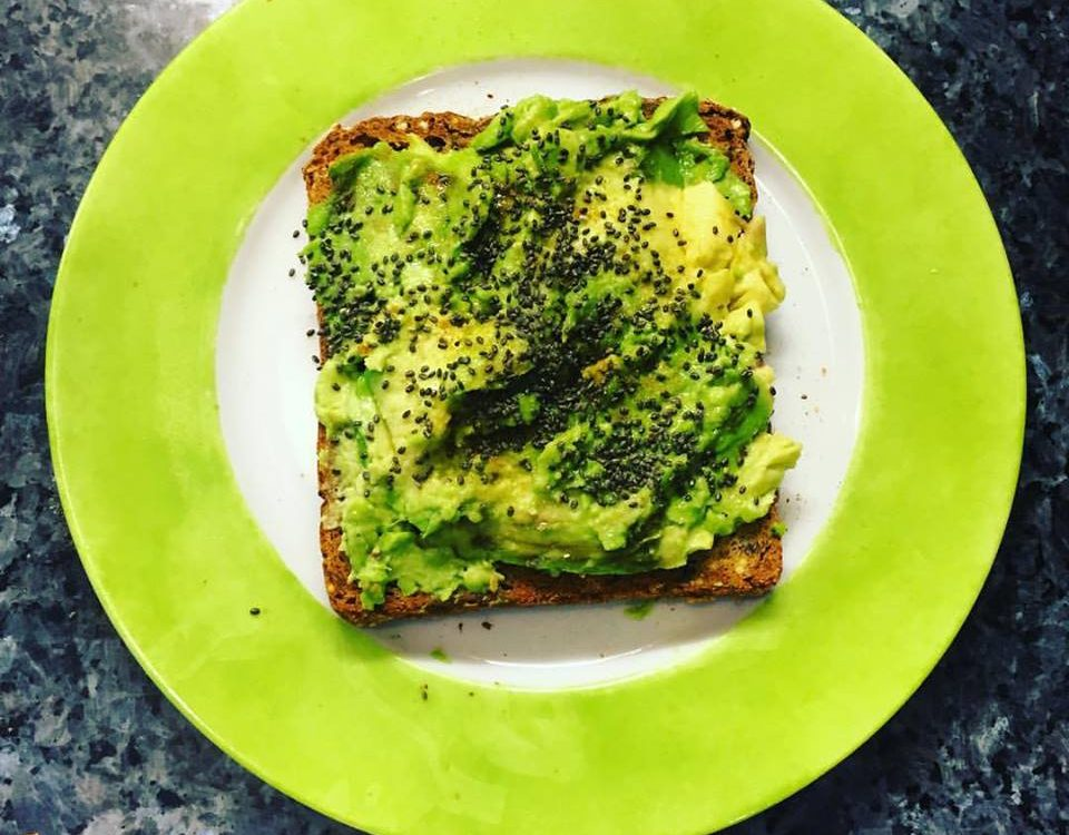 toast with avocado and spices on a green plate