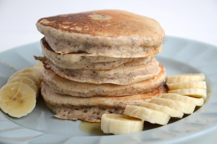 stacked pancakes on plate with banana slices
